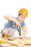 Perforación del trabajador manual con una máquina del sondeo a mano en un worksho Imagen de archivo