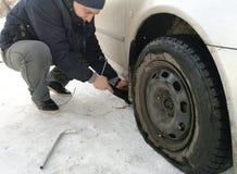 Perforado y neumático desinflado en el camino Reemplazo de la rueda por un enchufe por el conductor foto de archivo libre de regalías