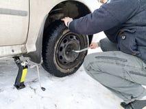 Perforado y neumático desinflado en el camino Reemplazo de la rueda por un enchufe por el conductor imagen de archivo
