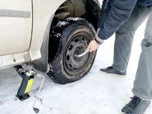 Perforado y neumático desinflado en el camino Reemplazo de la rueda por un enchufe por el conductor fotografía de archivo