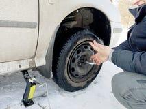 Perforado y neumático desinflado en el camino Reemplazo de la rueda por un enchufe por el conductor fotos de archivo