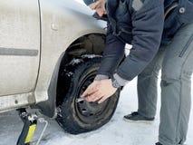 Perforado y neumático desinflado en el camino Reemplazo de la rueda por un enchufe por el conductor imagenes de archivo
