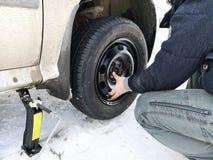Perforado y neumático desinflado en el camino Reemplazo de la rueda por un enchufe por el conductor imágenes de archivo libres de regalías