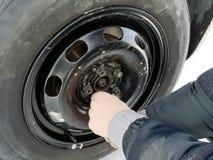 Perforado y neumático desinflado en el camino Reemplazo de la rueda por un enchufe por el conductor foto de archivo