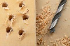 Perforare un pozzo in legno Trapano e compensato di legno in un'officina di carpenteria fotografia stock