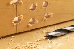 Perforare un pozzo in legno Trapano e compensato di legno in un'officina di carpenteria immagini stock