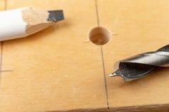 Perforare un pozzo in legno Trapano e compensato di legno in un'officina di carpenteria immagine stock