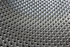 Perforated bright metal. For background Royalty Free Stock Image