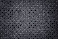 Perforated dark gray leather texture background, closeup. Black backdrop from wrinkle skin royalty free stock photos