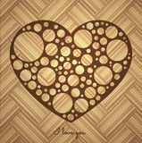 Perforated heart. Perforated brown heart on a wooden background Royalty Free Stock Image