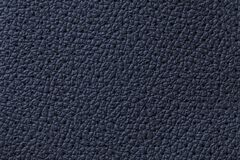 Perforated navy blue leather texture background, closeup. Denim backdrop from wrinkle skin stock photography