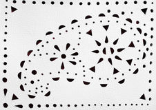 Perforated paisley figure on white leather Stock Photo
