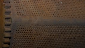 Perforated thick iron object, gear in corner. Machine, unfocused background stock photo