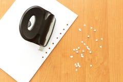 Perforateur de trou avec le papier sur la table de bureau Image stock