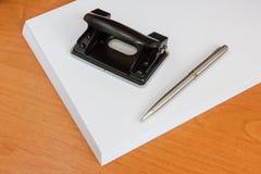 Perforateur de trou de bureau et un crayon lecteur sur une pile de papier Images libres de droits