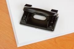 Perforateur de trou noir de bureau sur une pile de papier. Images libres de droits