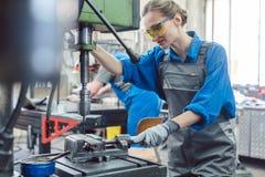 Perforatrice di funzionamento della donna del lavoratore del metallo fotografie stock libere da diritti