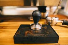 Perforazione del caffè espresso che mette su vassoio con la polvere rimanente del caffè espresso fotografia stock
