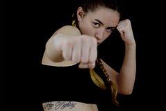 Perforazione di pugilato di addestramento della ragazza su fondo nero Fotografia Stock
