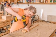 Perforazione femminile del falegname nel bordo Fotografie Stock Libere da Diritti