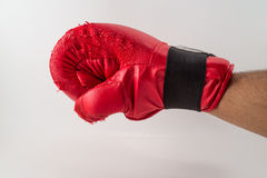 Perforazione rossa, braccio maschio. Glooves rossi di pugilato. Addestramento, sport. Immagine Stock Libera da Diritti