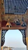 Perforerad wood panel- och bambulampskugga dekorerar sjösidagazeboen Arkivbilder