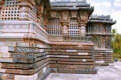 Perforerade fönster och utsmyckad baslättnad, norr östlig vägg, Kedareshwara tempel, Halebid, Karnataka royaltyfria foton