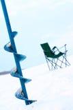 Perfori per ghiaccio e una presidenza per pesca di inverno Fotografia Stock Libera da Diritti