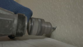 Perfori un pozzo nella parete e martella il perno archivi video