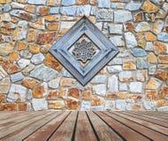 Perforiertes Holz verziert auf alter Steinwand Stockbilder