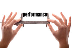 Performace. Color horizontal shot of two hands holding a caliper and measuring the word performance Royalty Free Stock Photos