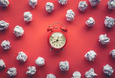 Performance concepts with paper crumpled ball and alarm clock on worktable background.Time and dateline. Top view images royalty free stock images