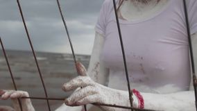 Performance female in white paint leans on cage on sea shore along metal fence. Performance artist caucasian female covered in white paint with red hair, tank stock footage