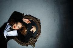 Performance with a girl and mirror. Fashion portrait of young brunette with hairstyle, red lips Royalty Free Stock Images
