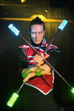 Performance of a man with tattoo and terrible pupils. In samurai garb with glow sticks, sticks crossed in front of him stock photography