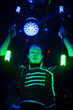 Performance of a man with a terrible pupils in samurai garb. With glow sticks in stage with light ball stock photography