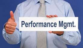 Performance Management - Businessman with sign. And thumb up on blue background royalty free stock image