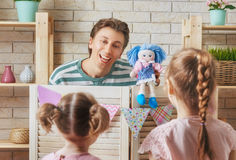 Performance in the puppet theater. Happy loving family. Father and his daughter in kids room. Funny dad and lovely child having fun and playing performance in Stock Image
