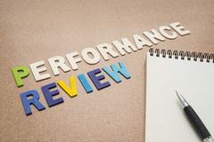 Performance review text with open spiral notebook and pen Royalty Free Stock Photos
