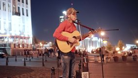 Performance of a street musician with a guitar on the night street of the big city. Great atmosphere of rest and comfort. City stock video footage