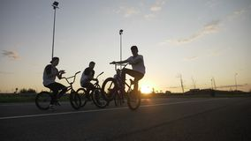 Performance of a biker riding on one wheel cycle in front of a crowd formed by his bicyclist friends at sunset in slow motion -. Performance of young biker stock footage