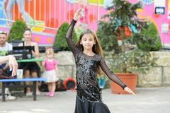 Performance of a young dancer. Little girl dance poses. Speech by a young girl in a black dress. Swinging a yellow fan royalty free stock photography