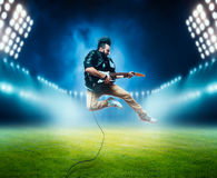 Performer with electro guitar on the stadium stage. Male performer with electro guitar in a jump on the stadium stage with the decorations of lights. Music Stock Photography