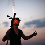 Performer fanning a spark into a fire Stock Photography