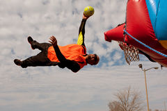 Performer Gets Sideways In Midair Attempting To Dunk Ball. Hampton, GA, USA - February 28, 2015:  An entertainer uses a mini-trampoline to get parallel to the Stock Photography