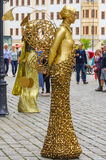 Performer - gold painted artists on a city street, living statues Stock Photos