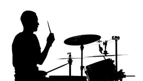 Performer plays professional music on drums. White background. Silhouettes. Side view. Performer sitting on a chair plays professional good music on a stock video