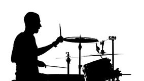 Performer plays professional music on drums. White background. Silhouettes. Side view. Slow motion. Performer sitting on a chair plays professional good music on stock video footage