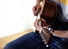 The performer plays a wooden acoustic guitar stock photo