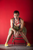 Performer seated backstage. Male performer seated backstage in front of red wall Stock Photography